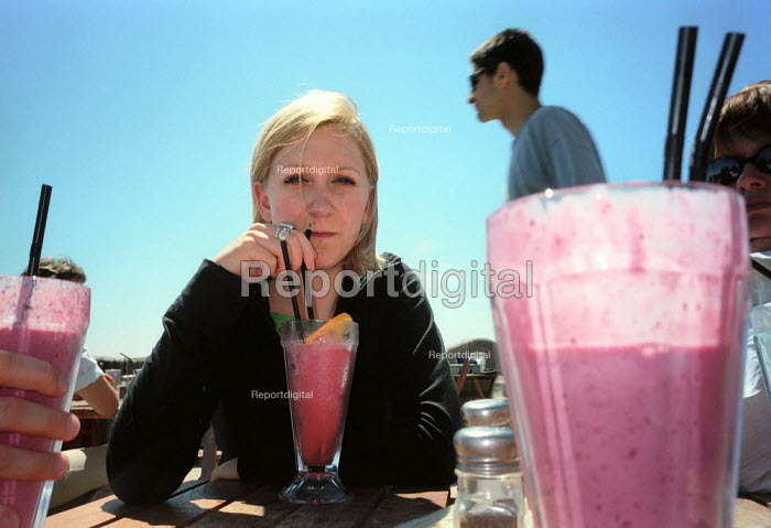 Young woman drinking a smoothie at an open air cafe. - Paul Carter - 2001-06-20