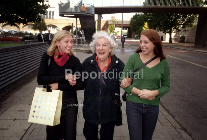 Two sisters and their grandmother walking along a city street, arm in arm. - Paul Carter - 2001-09-15