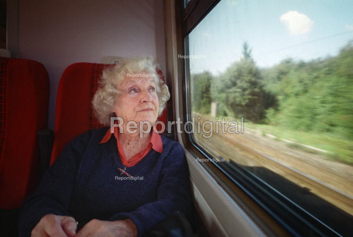 Elderly woman sitting in a train carriage, looking out of the window as the countryside speeds past. - Paul Carter - 2001-09-15