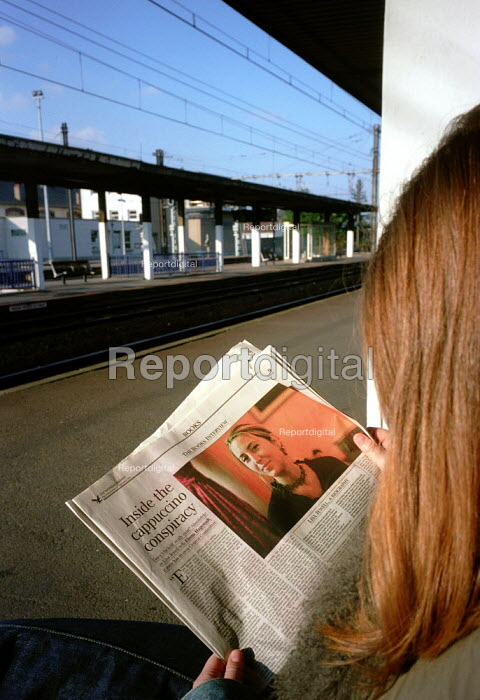 Young woman reading a paper whilst waiting for her train. - Paul Carter - 2001-09-23