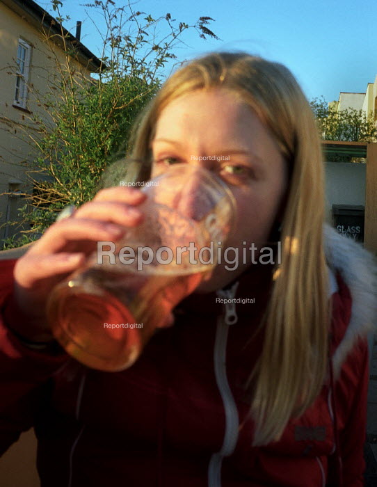 A teenage girl drinking a pint of beer in a pub beer garden. - Paul Carter - 2002-04-30