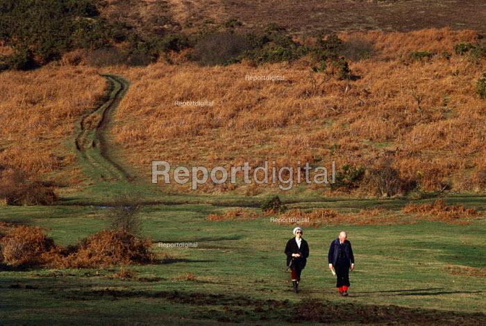 An elderly couple walk across heathland in the New Forest. - Paul Carter - 1989-09-10