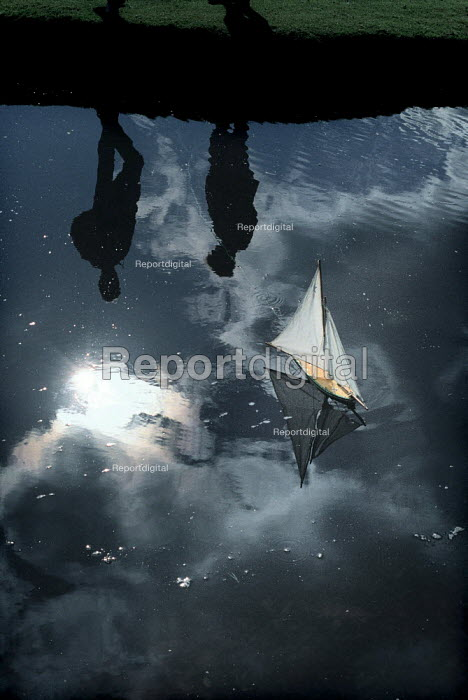 Reflections of two people sailing a model boat on a pond. - Paul Carter - 1987-10-18