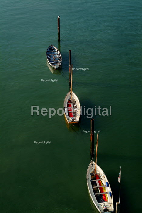 Small sailing boats tied to mooring posts on green water. - Paul Carter - 2003-09-04