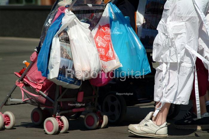 Woman pushing a pram laden with shopping bags. - Paul Carter - 2003-09-04