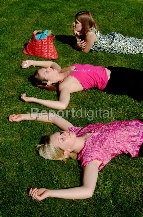Three young women lying on the grass, sunbathing. - Paul Carter - 2003-07-12