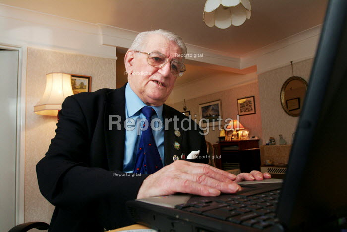 Elderly man using his laptop computer at home. - Paul Carter - 2003-12-18