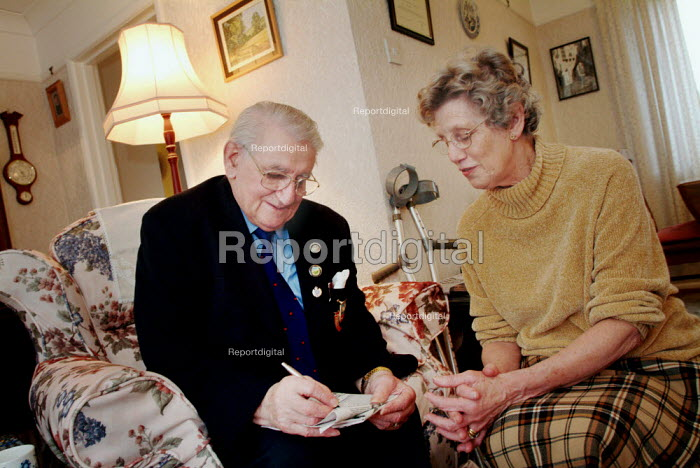 Elderly couple completing a newspaper crossword. - Paul Carter - 2003-12-18