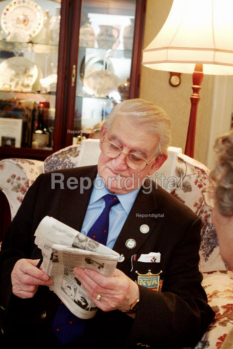 Elderly man completing a newspaper crossword at home - Paul Carter - 2003-12-18