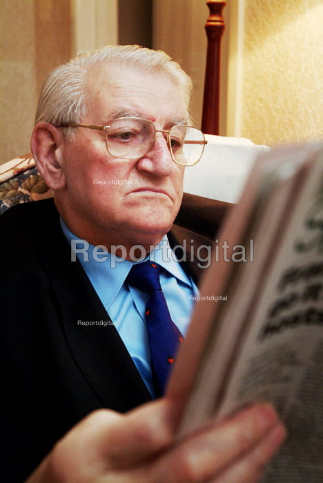 Elderly man sitting in an armchair, reading his newspaper at home. - Paul Carter - 2003-12-18