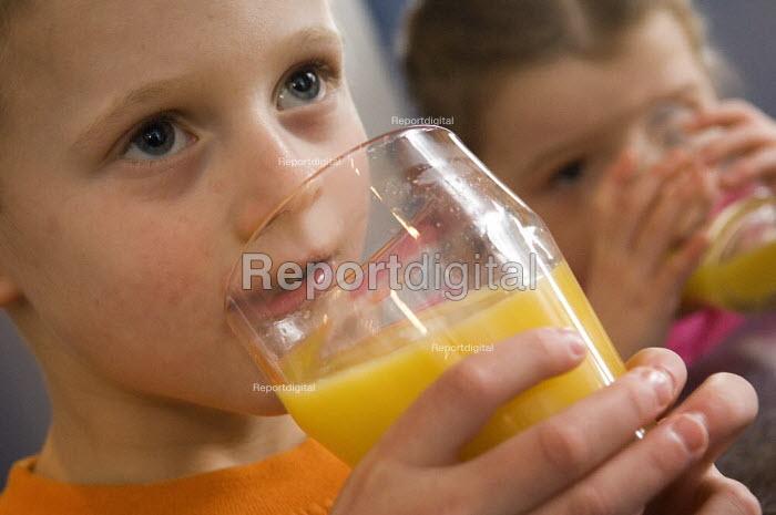 Children drinking glasses of orange juice. - Paul Carter - 2006-01-07