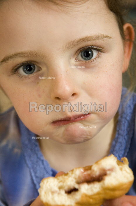 Young girl eating a doughnut. - Paul Carter - 2006-01-07