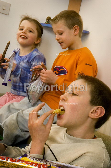 Children eating unhealthy snacks sitting on a sofa. - Paul Carter - 2006-01-07