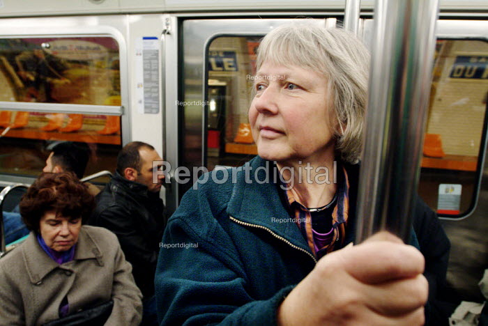 Woman holding on to a support bar while travelling on the... - Paul Carter, JP991242.jpg