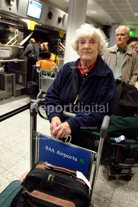 Elderly woman waiting in a queue at an airport check-in desk. She is pushing a trolley full of her luggage. - Paul Carter - 2003-10-15