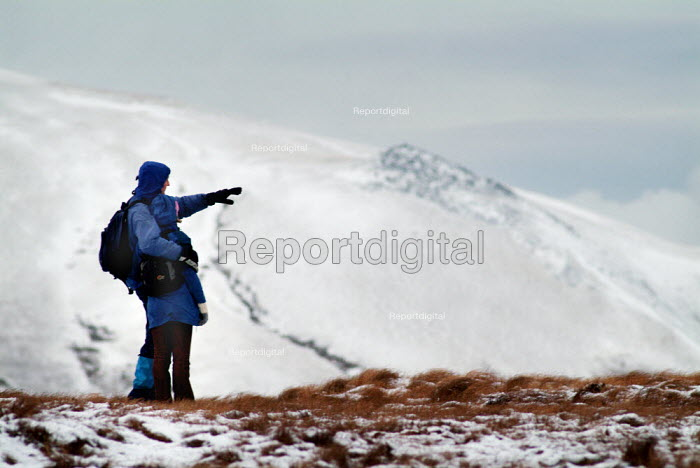 Two walkers stop and admire the view over snow covered hills. The Lake District. - Paul Carter - 2003-12-31