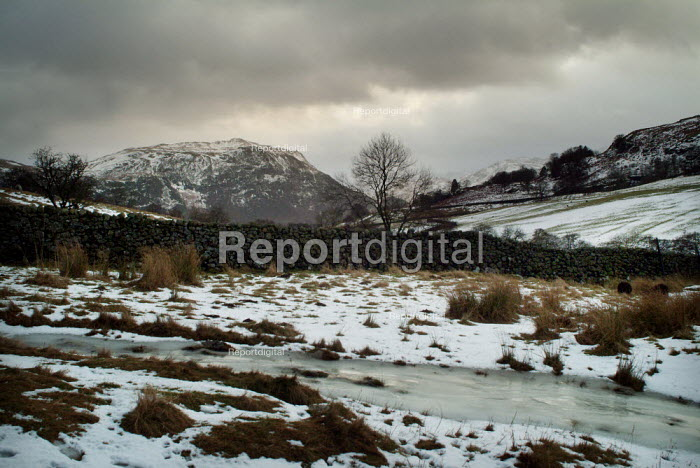 Winter landscape looking over a frozen river to a hill in the backgound. The Lake District. - Paul Carter - 2004-01-01
