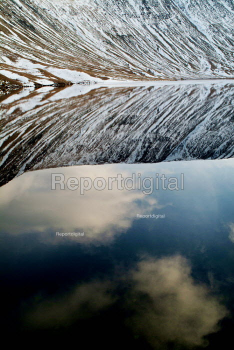 Snow covered hills reflect into the still water of a lake. The Lake District. - Paul Carter - 2004-01-02