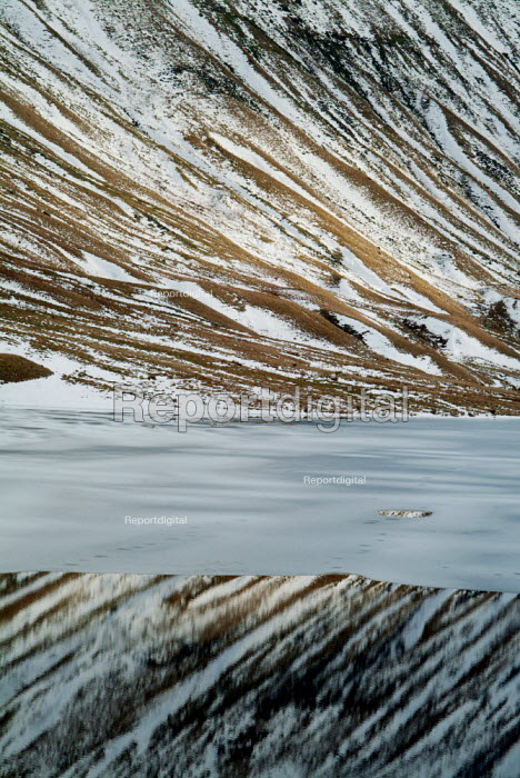 Snow covered hills reflect into the still water of a lake, some of which is covered by a sheet of ice. The Lake District. - Paul Carter - 2004-01-02