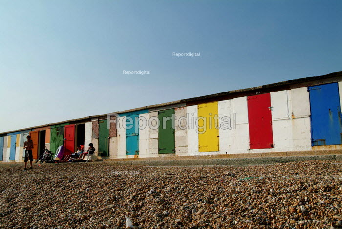 Family sitting out on a shingle beach, in front of row of brightly coloured doors of sea huts. Milford-on-Sea, Hampshire. - Paul Carter - 2003-05-29