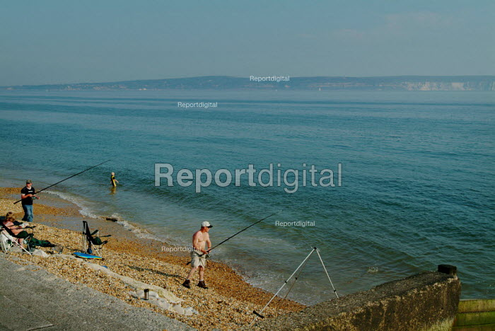 Two men fishing on the edge of the beach at Milford-on-Sea, Hampshire. - Paul Carter - 2003-05-29