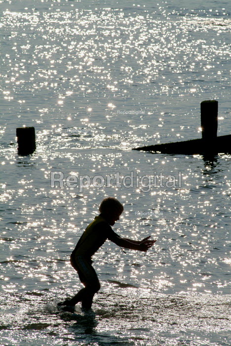 Silhouette of a young boy playing in the sea at Milford-on-Sea, Hampshire. - Paul Carter - 2003-05-29