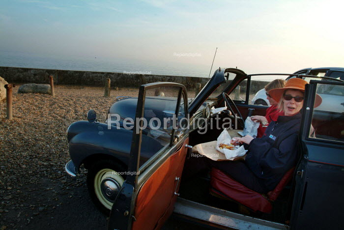 Two woman eating fish and chips, sitting in their car. Milford-on-Sea, Hampshire. - Paul Carter - 2003-05-29