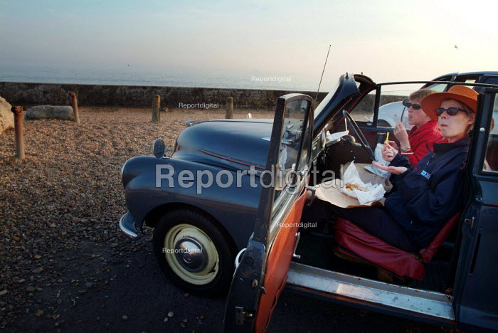 Two woman eating fish and chips, sitting in their car.