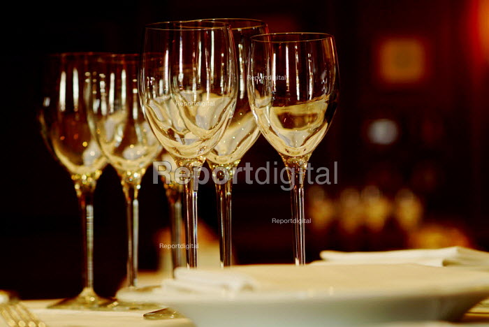 Clean sparkling wine glasses on a table in a restaurant, laid for the evening meal. - Paul Carter - 2004-07-27