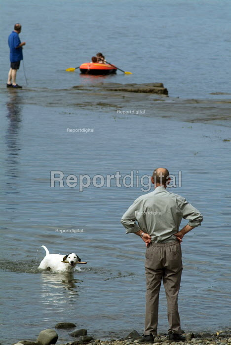 Man playing fetch with his dog on the beach. Dorset - Paul Carter - 2004-08-03