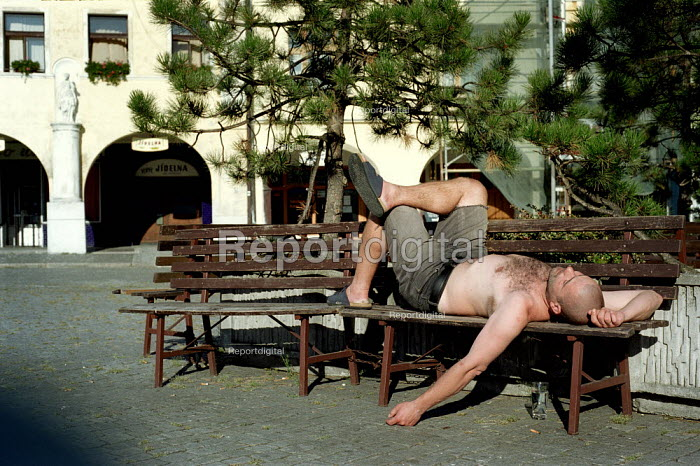 Man asleep on a bench in the square in the sun. Melnik north of Prague. Czech Republic - Paul Carter - 2003-08-18