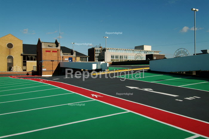 Brightly coloured tarmac of a the upper deck of an empty multi storey car park. Showing parking bays and pedestrian walkways. - Paul Carter - 2004-09-24