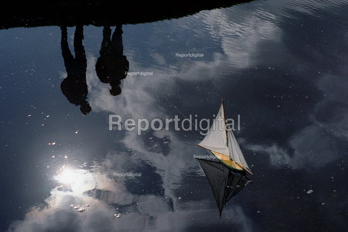 Reflection of two children sailing a model boat on a pond. - Paul Carter - 2003-10-18