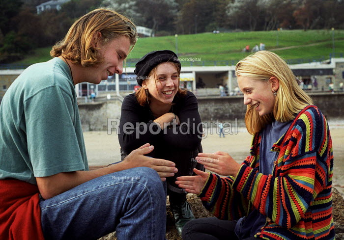 Brother and sisters sitting on a beach, playing slap hands. Cornwall. - Paul Carter - 1993-10-06