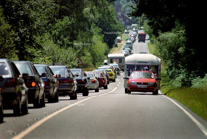 Car towing a carvan, passing a queue of traffic heading into The New Forest on a Bank Holiday. - Paul Carter - 1990-08-26