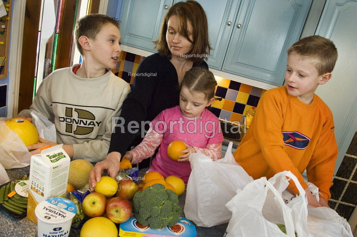 Children unpacking plastic shopping bags with their mother - Paul Carter - 2006-01-07