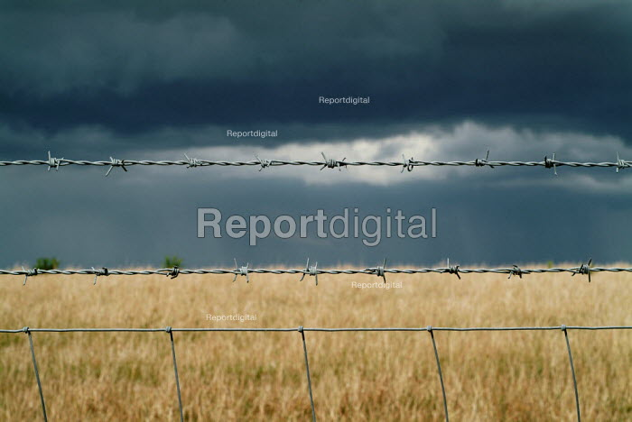Close up of a section of barbed wire fence surrounding a field. Dark storm clouds cover it.Views from South Downs way near Alfriston, East Sussex - Paul Carter - 2005-07-04