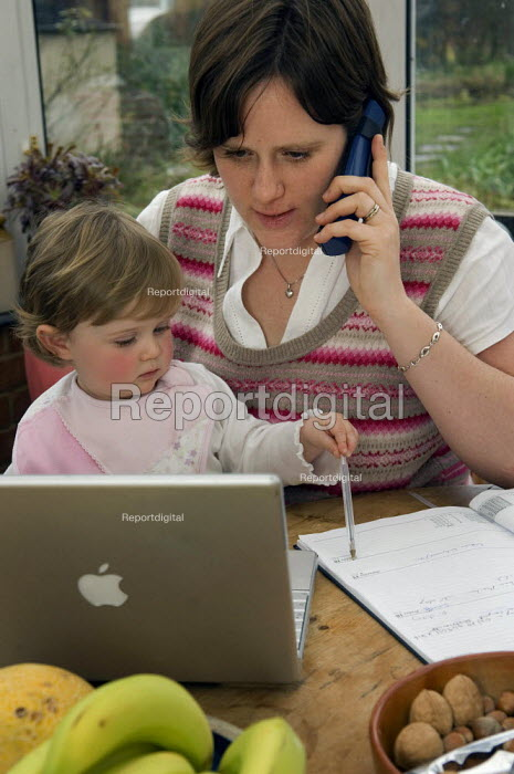 A mother works from home at a laptop with her daughter on... - Paul Carter, JP992162.jpg