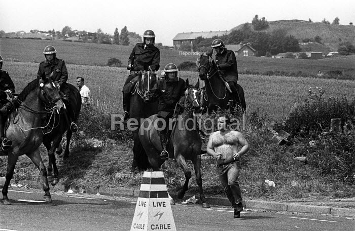 Riot police on horseback chase lone, bare-chested, striking miner at the Battle of Orgreave - a violent confrontation between police and picketing miners at the coking plant in South Yorkshire. The picket has retained his cigarette. - John Harris - 1984-06-18