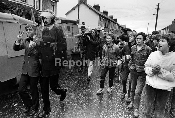RUC preventing loyalist march from passing along traditional route through catholic area, Portadown, Northern Ireland 1985. Young catholics jeer as loyalist band member is arrested. - John Sturrock - 1985-07-12