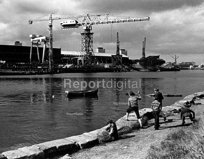 Children playing on the riverside infront of a shipyard, in Sunderland. Throwing stones into the river. - John Sturrock - 1980-07-10