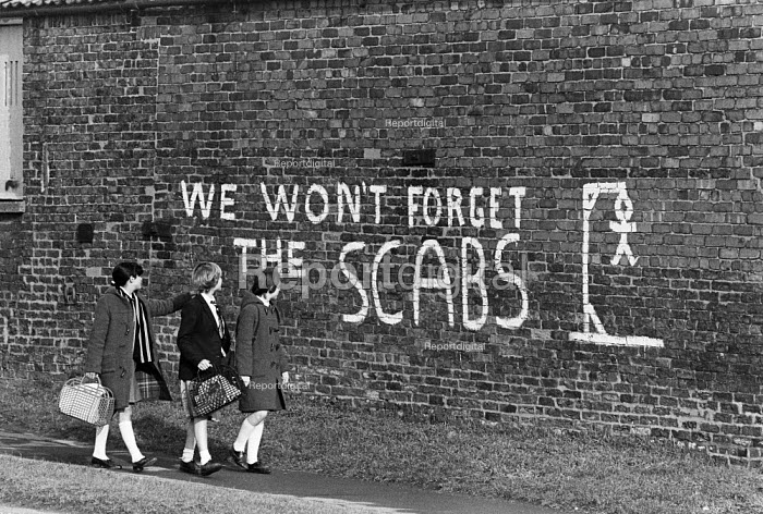 Children walk past graffiti We Wont Forget The Scabs and a scab hanging from a scaffold, bitterness remains at the end of the strike, Armthorpe, Yorkshire - John Sturrock - 1985-04-11