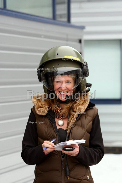 A journalist smiling in a big safety helmets as members of the press wait to board one of the new Chinook MK3 helicopters at RAF Odiham in Hampshire. - Justin Tallis - 2010-01-13