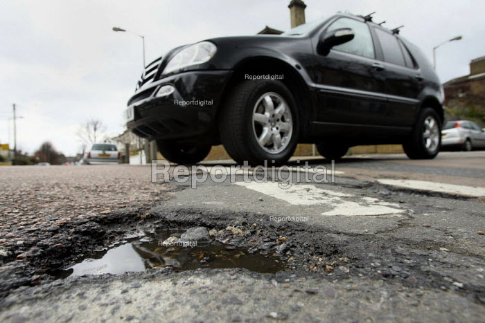Potholes on a residential street being avoided by drivers... - Justin Tallis, JT1003223.JPG
