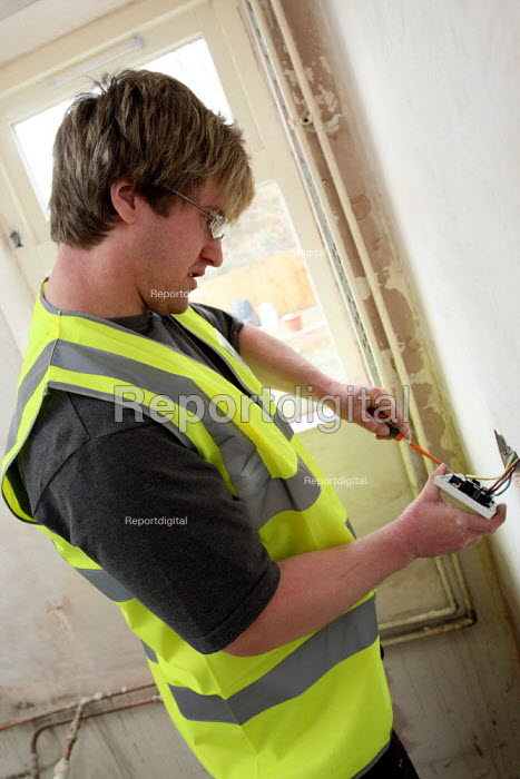 Apprentice working towards his NVQ level 3 electrical. Being taught by an experienced electrician whilst working for Nottingham City Homes, One In A Million Scheme. Nottingham. - Justin Tallis - 2010-03-17