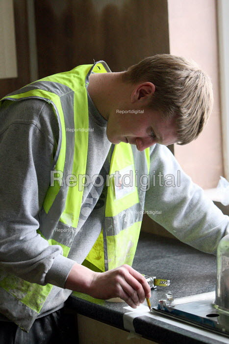 Apprentice working towards his NVQ level 2 in carpentry and joinery. Measuring up the space where he will install a kitchen sink whilst working for the Nottingham City Homes, One In A Million Scheme. - Justin Tallis - 2010-03-17
