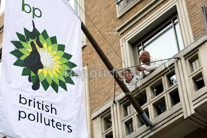 Greenpeace protesters on a balcony at BP headquarters hang a flag saying British Polluters in protest at the BP oil spill in the Gulf of Mexico. St James's Square, London. - Justin Tallis - 2010-05-20