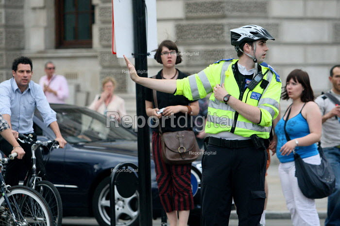 Police Community Support Officer directing heavily congested traffic during rush hour, London - Justin Tallis - 2010-07-02