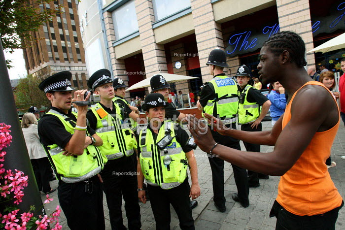 A black man holding his hands up asking not to be filmed by a Police Evidence Gathering Team (EGT). The man was passing an English Defence League Protest. Luton. - Justin Tallis - 2010-07-22