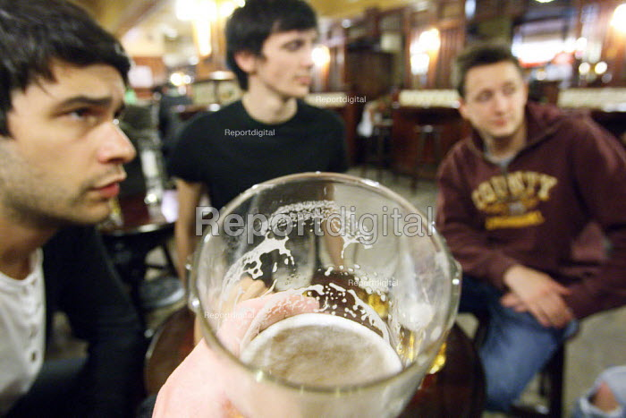 Young men having a early evening pint in the pub after... - Justin Tallis, JT1008447.JPG